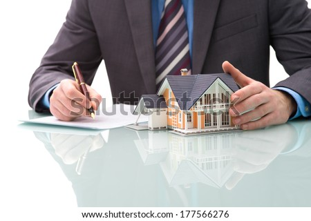 Man signs purchase agreement for a  house - stock photo