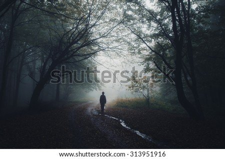 man silhouette at the edge of a dark forest - stock photo