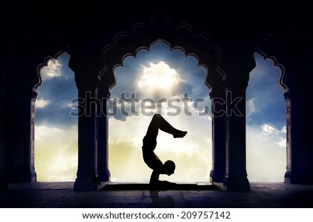 Man silhouette doing yoga advance scorpion pose in old temple at sunset sky background - stock photo