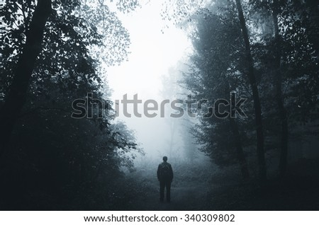 man silhouette in dark foggy forest - stock photo