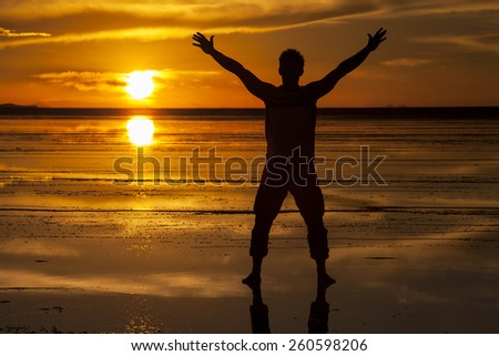 Man silhouette in Salar de Uyuni, Bolivia, in the sunset light. Reflection of the sun and the clouds in the salt - stock photo