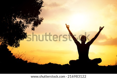 Man silhouette in Yoga meditation pose with rising hands near the tree at sunset in Gokarna, Karnataka, India - stock photo