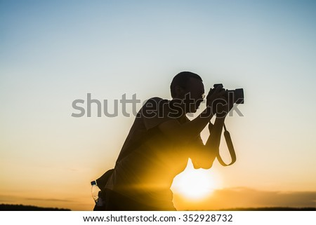 man Silhouette of Young adult female Photographer silhouette at Sunset light rays Cute girl hold professional digital camera with bag against blue and yellow sky background. Sun rays. - stock photo
