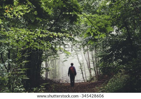 man silhouette on forest path - stock photo