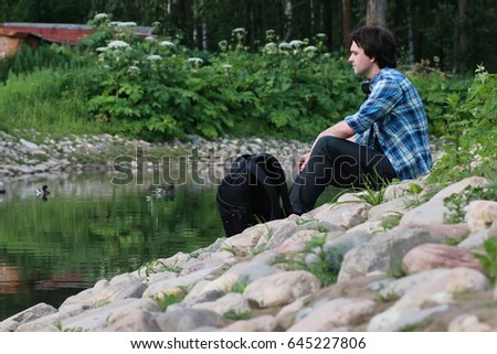 man sit on stone river