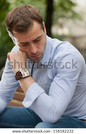 Man sits on the bench and relax in the public garden