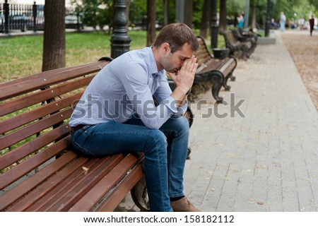 Man sits on the bench in the public garden