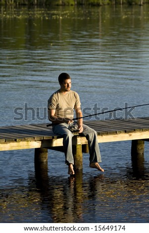 Man sitting alone on a pier fishing in a bay. - stock photo