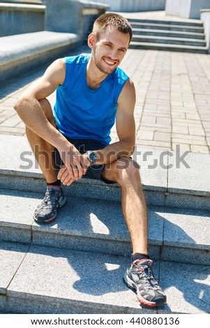 man sitting and resting on the steps. man runner athlete warming up before jogging along a city bay at the early morning. man fitness sunset jogging workout wellness concept. - stock photo