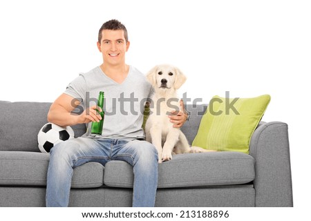Man sitting at couch with his puppy and football isolated on white background - stock photo