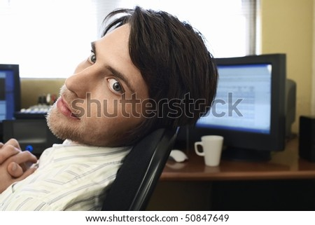 Man sitting at desk with computers. - stock photo