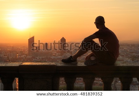 Man sitting at Fourviere Basilica, enjoying the sunrise over the city of Lyon, France.