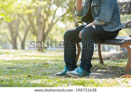 Man sitting at the natural park. Exhausted or stressed of Male in blue jean and jacket  with copy space.