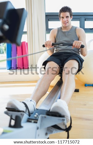 Man sitting at the row machine at the gym smiling