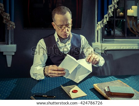 Man sitting at the table and opens a letter