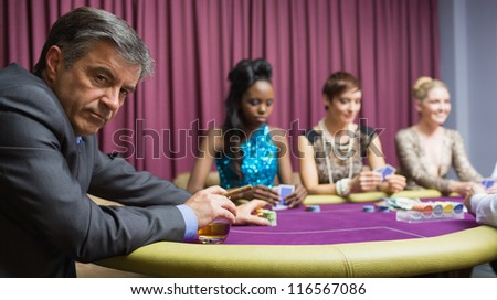 Man sitting at the table at the casino looking angry - stock photo