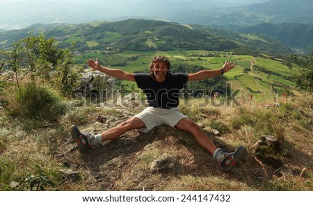 man sitting at the top of a mountain, achievement concept - stock photo
