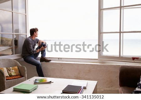 Man Sitting At Window And Looking At Beautiful Beach View - stock photo