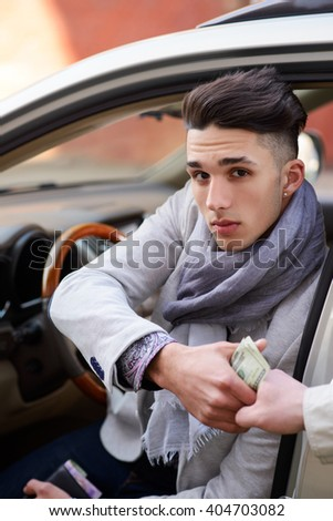 man sitting behind the wheel of the car gives money to another man