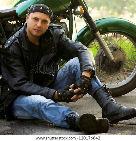 Man sitting by motorcycle - stock photo