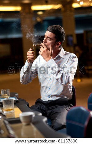man sitting by the slot machine, lighting confident a cuban cigar - stock photo