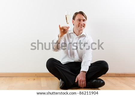 Man sitting cross-legged on the wooden floor of his apartment - stock photo
