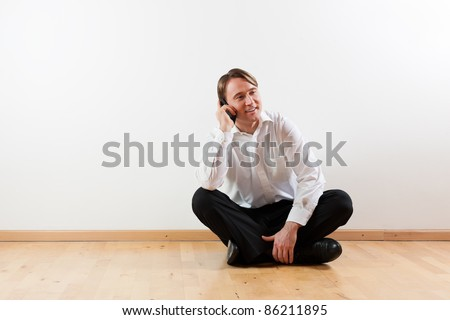 Man sitting cross-legged on the wooden floor of his apartment and is making a phone call - stock photo