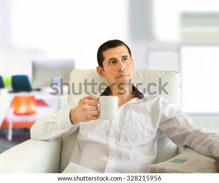 man sitting drinking tea and thinking at the lounge of the office - stock photo