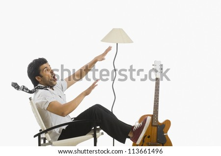 Man sitting in a chair and trying to control himself in a storm - stock photo