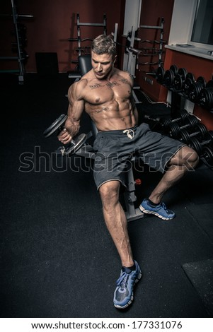 Man sitting in a gym with a dumbbell