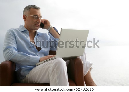 Man sitting in an armchair with a laptop computer and a phone - stock photo