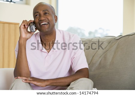 Man sitting in living room using telephone and smiling - stock photo