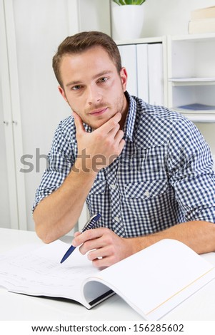 Man sitting in office and reading document - stock photo