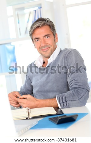 Man sitting in office in front of laptop computer - stock photo