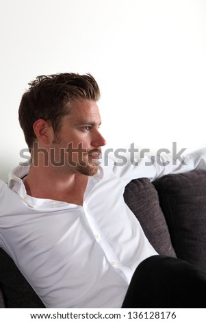 Man sitting in sofa looking away from camera wearing a white shirt and black trousers.  White background. - stock photo