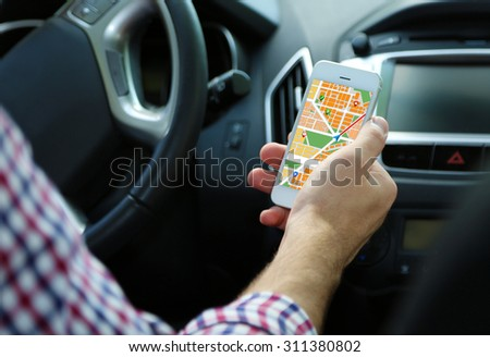 Man sitting in the car and holding smart phone with map gps navigation application - stock photo