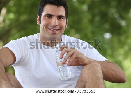 man sitting in the park and drinking water - stock photo