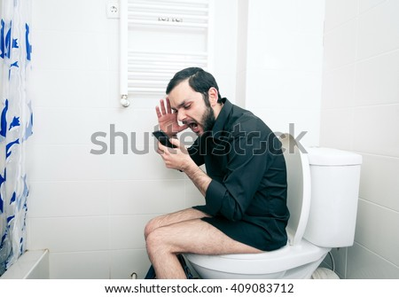 man sitting in toilet and talking on phone - stock photo