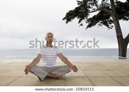 Man sitting in yoga position on terrace by infinity pool - stock photo