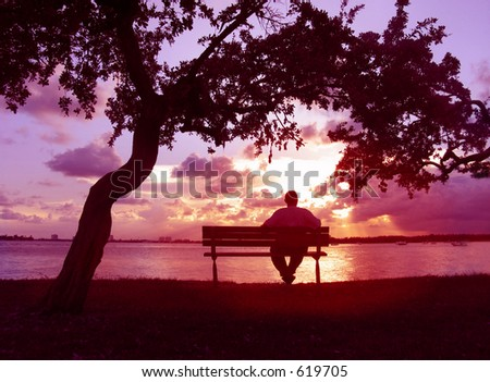 Man sitting on a bench enjoying sunset on the lake - stock photo