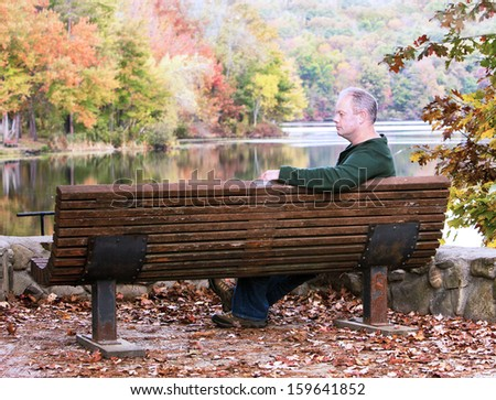 Man sitting on a bench near the lake in autumn