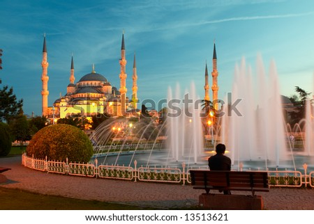 Man sitting on a bench opposite of blue mosque in Istanbul - stock photo