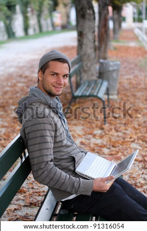Man sitting on a Bench with notebook smiling - stock photo