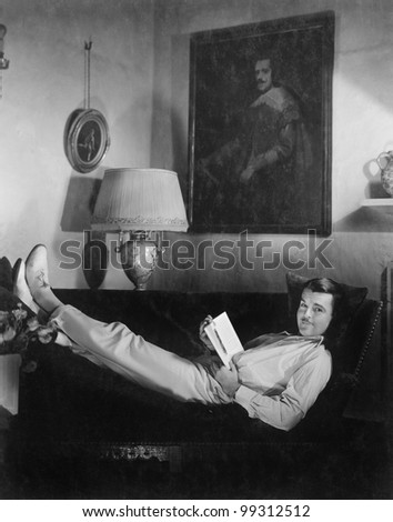 Man sitting on a couch reading a book - stock photo