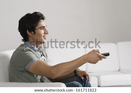 Man sitting on a couch watching television - stock photo