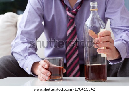 Man sitting on a couch with glass and bottle of whiskey - stock photo