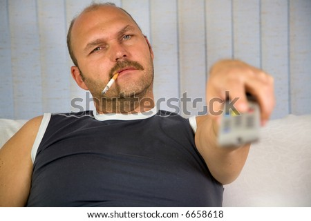 Man sitting on a couch with the remote and a cigarette in his mouth - stock photo
