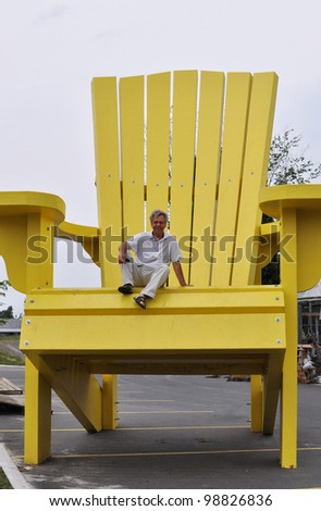 Man sitting on a giant chair - stock photo
