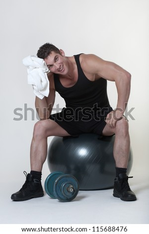 man sitting on a gym ball holding a towel after doing a work out - stock photo