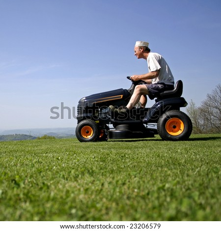 man sitting on a lawnmower in his garden - stock photo